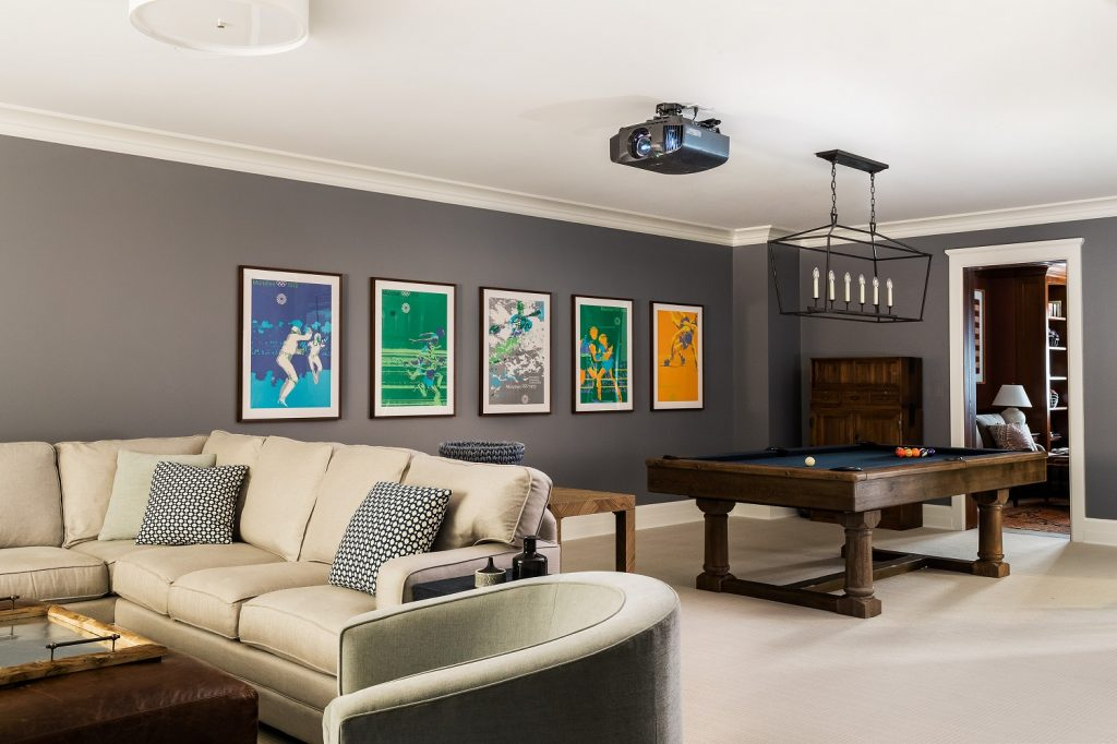 Recreation room with vintage posters, billiards table and sectional sofa