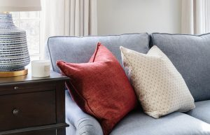 Red and cream sofa throw pillows on blue standard sofa