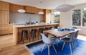 Mid-century modern kitchen with custom wood cabinets and blue accents