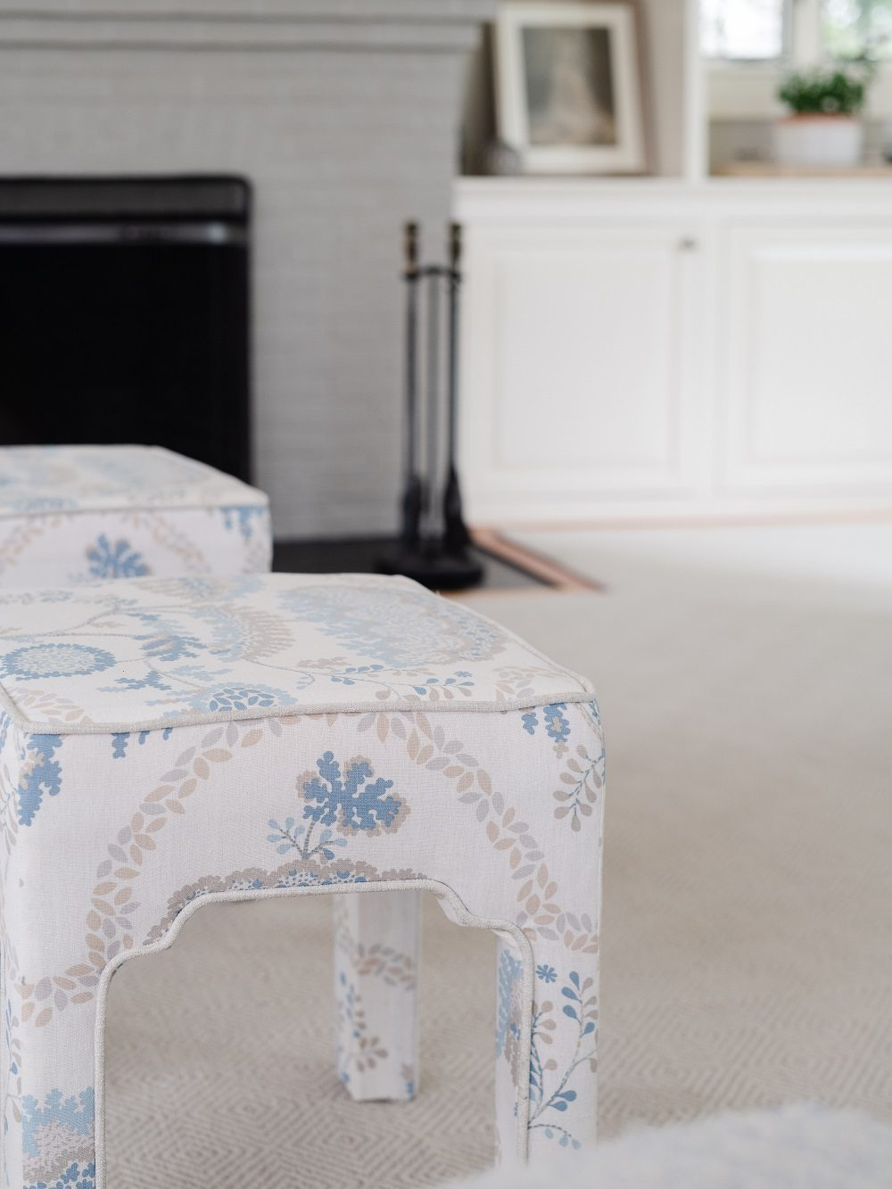 Detail of custom upholstered footstools with blue patterned fabric