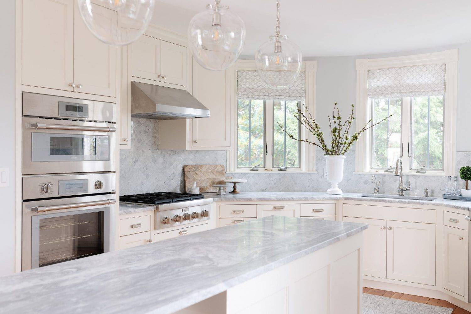White and gray kitchen with white cabinets and gray tile backsplash and marble countertops
