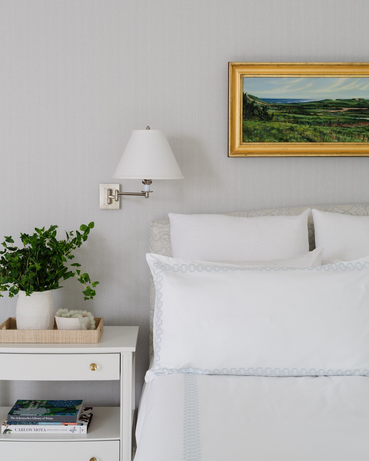 Master bedroom with white bedding and polished nickel wall sconces