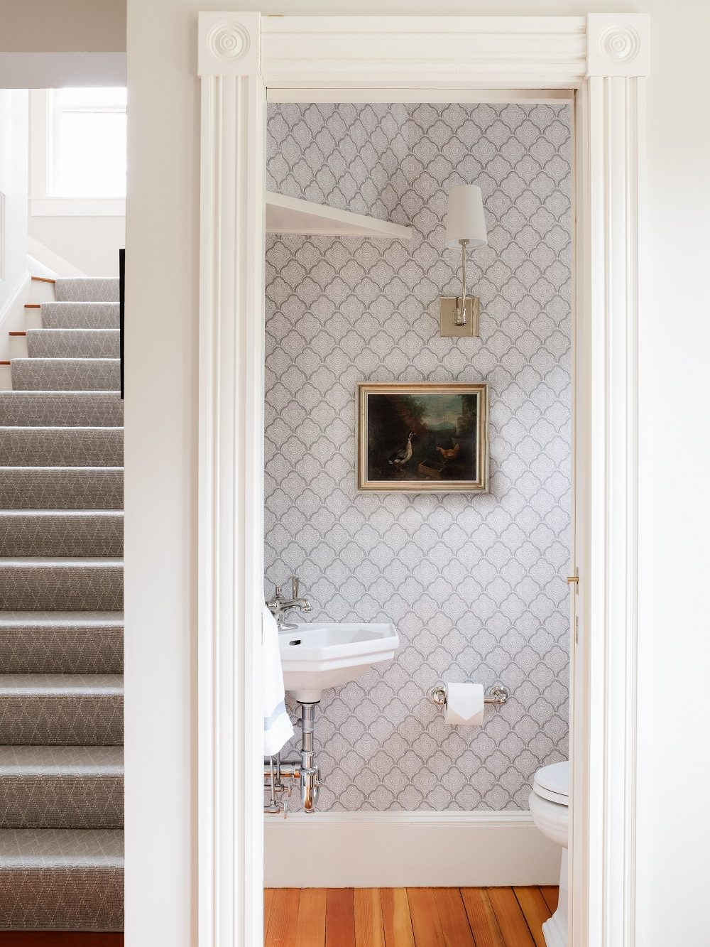 Powder room with corner sink and patterned wallpaper