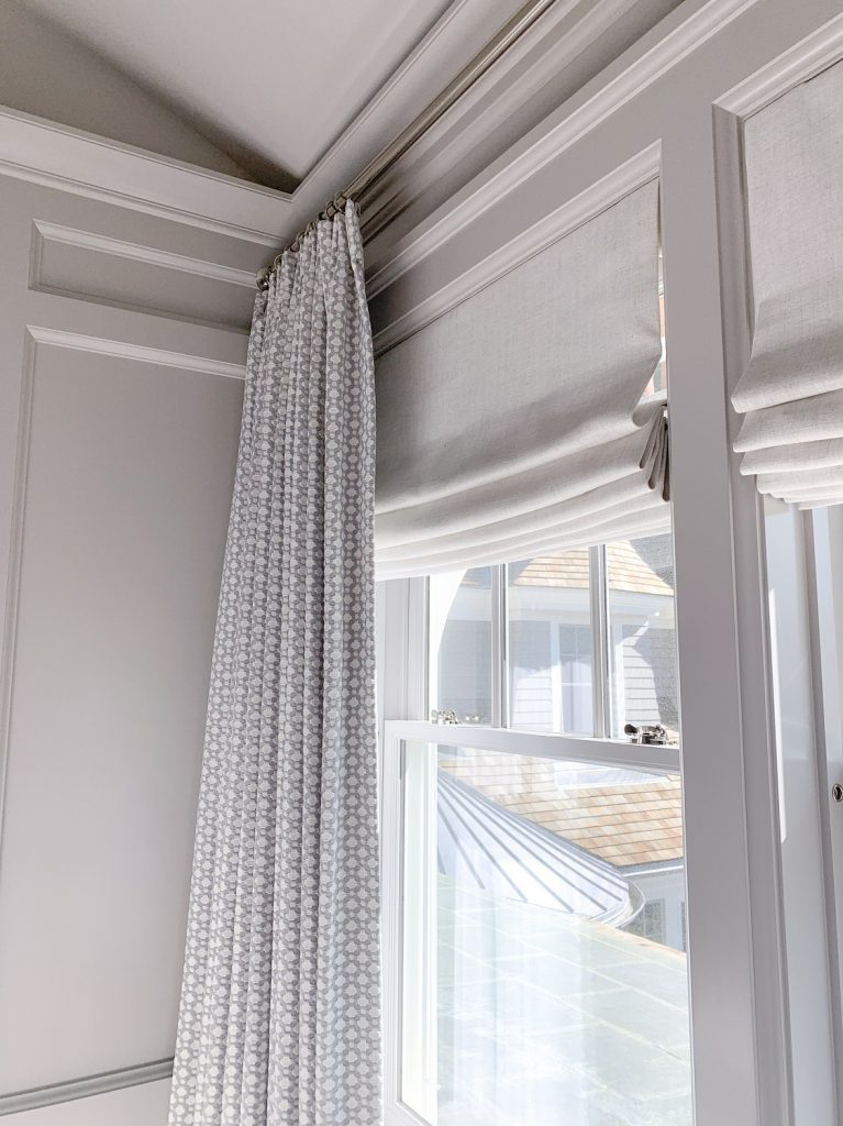 Layered window treatments with curtains paired with shades