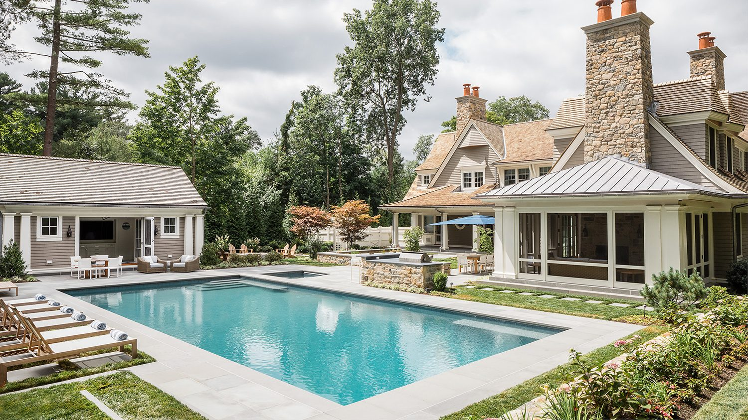 Outdoor space with poolside lounge chairs, screened porch and pool house