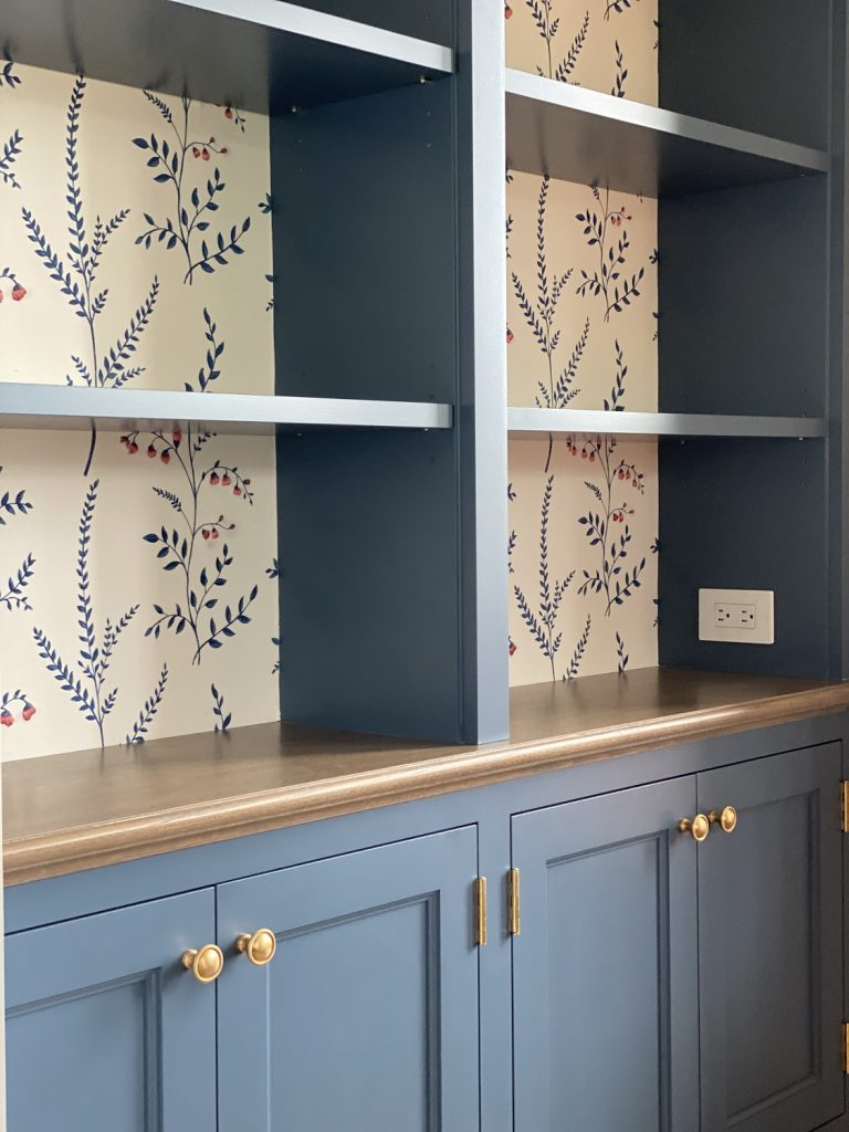 Textured wall covering behind bookshelves
